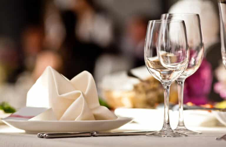 Plate with napkin and empty wine glasses at restaurant